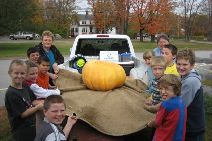 kids around large pumpkin in back of pickup
